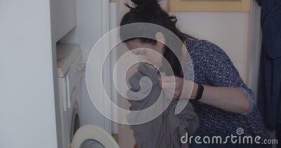 Happy attractive young woman loading laundry in the washing machine at home stock video