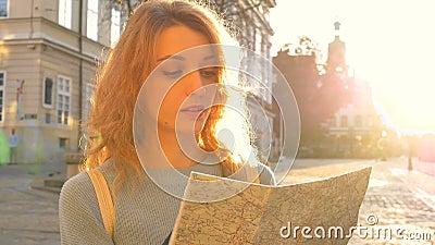 Happy aufgeregte erwachsene Mädchen sieht sich die Papierkarte an und sucht nach der Richtung am frühen Morgen in der Antike stock video