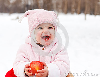 Happy baby with apple in winter park