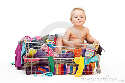 Happy baby in basket with clothes