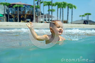 Happy baby boy enjoys swimming in sea waves