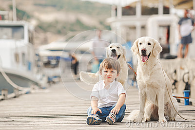 Happy baby boy with him dog on berth in summer