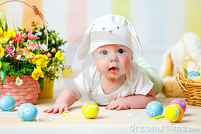 Happy baby child with Easter bunny ears and eggs and flowers Stock Photo