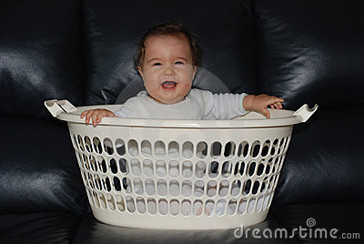 Happy baby in a clothes-basket