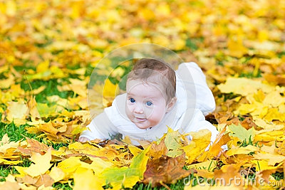 Happy baby girl in autumn park on yellow leaves
