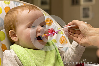 Happy Baby girl eating porridge