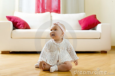Happy baby girl seated on a hardwood floor