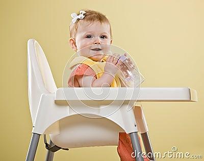 Happy baby girl sitting in highchair