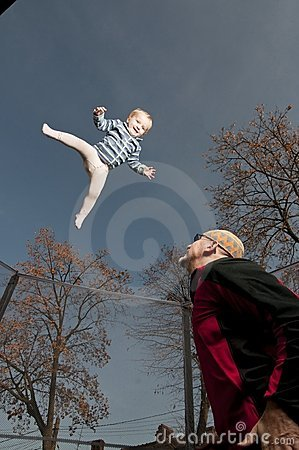 Happy baby jumping up on trampoline