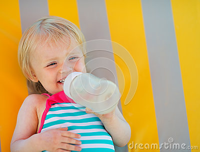 Happy baby laying on sunbed and drinking water