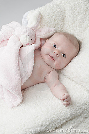 Happy baby with pink toy bunny blanket