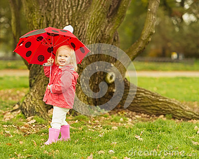 Happy baby with red umbrella outdoors