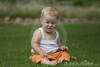 Happy baby sitting on grass