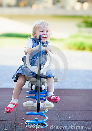 Happy baby swinging on horse on playground