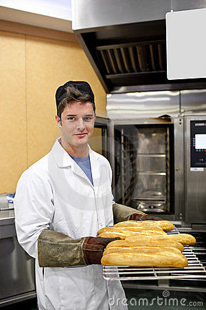 Happy baker showing his baguettes in his bakery
