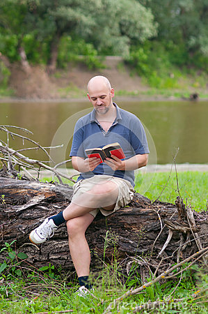 Happy bald man reading the book