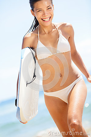 Happy beach fun woman surfer laughing in water