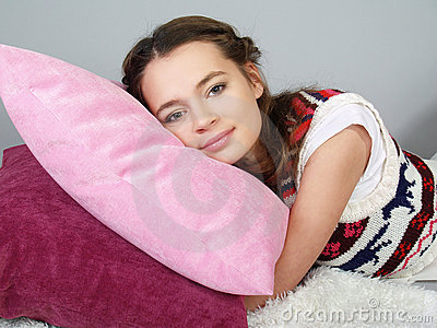 The happy beautiful girl lies on pink pillows