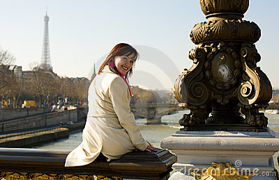 Happy beautiful girl sitting on bridge balustrade