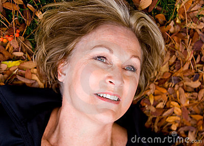 Happy, beautiful, mature woman in fall leaves