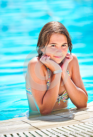 Happy beautiful teen girl smiling at the pool