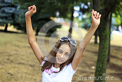 Happy beautiful teen raise her arms in park