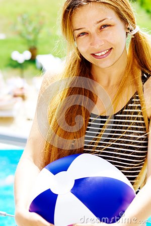 Happy beautiful woman with ball on holiday