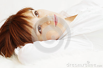 Happy beautiful woman lying on white fur plaid