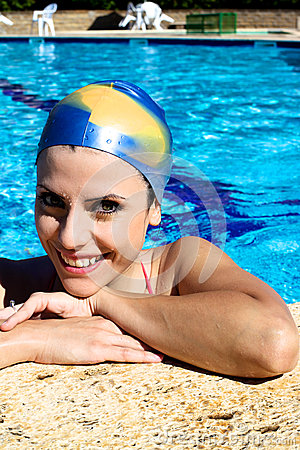 Happy beautiful woman in swimming pool with cap smiling