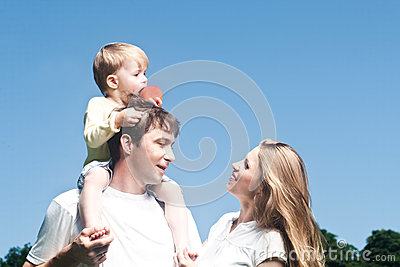 Happy beautiful young family posing outdoors.