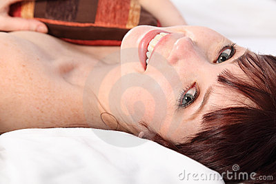 Happy beautiful young woman in bed lovely smile