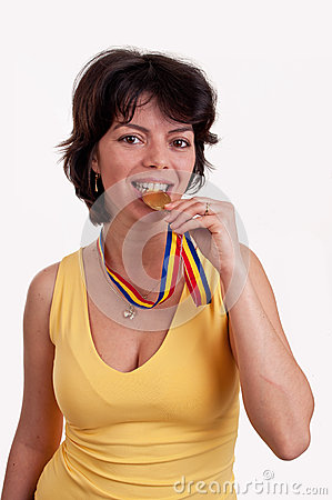 Happy beautiful young woman with gold medal between her teeth trying metal