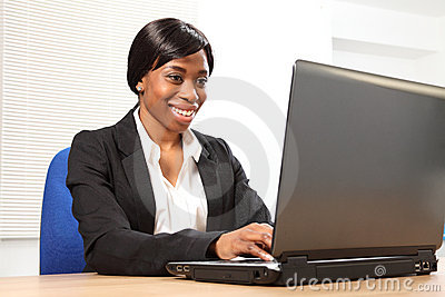 Happy black woman using laptop at office desk