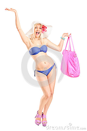 Happy blond female in swimsuit holding a beach bag