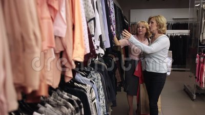 Happy blond women looking through clothes on rack stock video footage