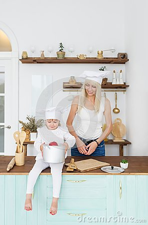 Free Happy Blonde Mother And Little Daughter In White Cap In Home Kitchen. Stock Photos - 122022953