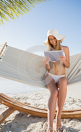 Happy blonde sitting on hammock using tablet pc
