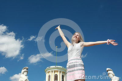 Happy blonde woman with arms raised