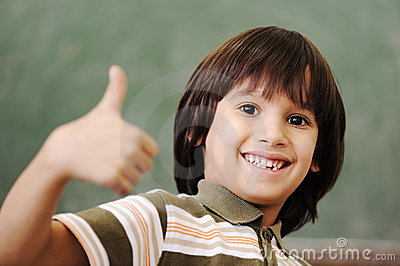 Happy boy in classroom with thumb