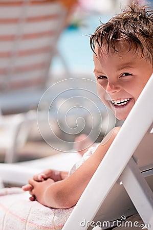 Happy boy on deck chair