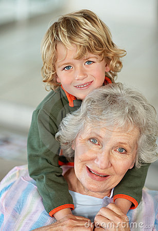 Happy boy embracing his grandmother from back