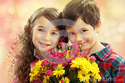 Happy boy and girl with bouquet of flowers.