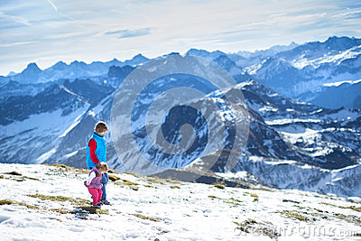 Happy boy with his baby sister in snow mountains