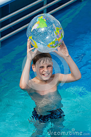 Happy boy hold inflatable globe  in pool