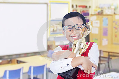 Boy holding trophy in classroom