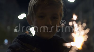 Happy boy holding lit firework sparkle at Christmas eve, celebration with family. Stock footage stock video