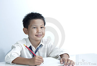 A happy boy holding pencil on white background