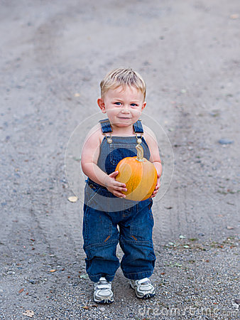 Happy boy holding pumpkin