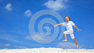 Happy boy jumping on beach