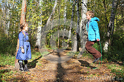 Happy boy jumps with skipping rope and girl looks at him